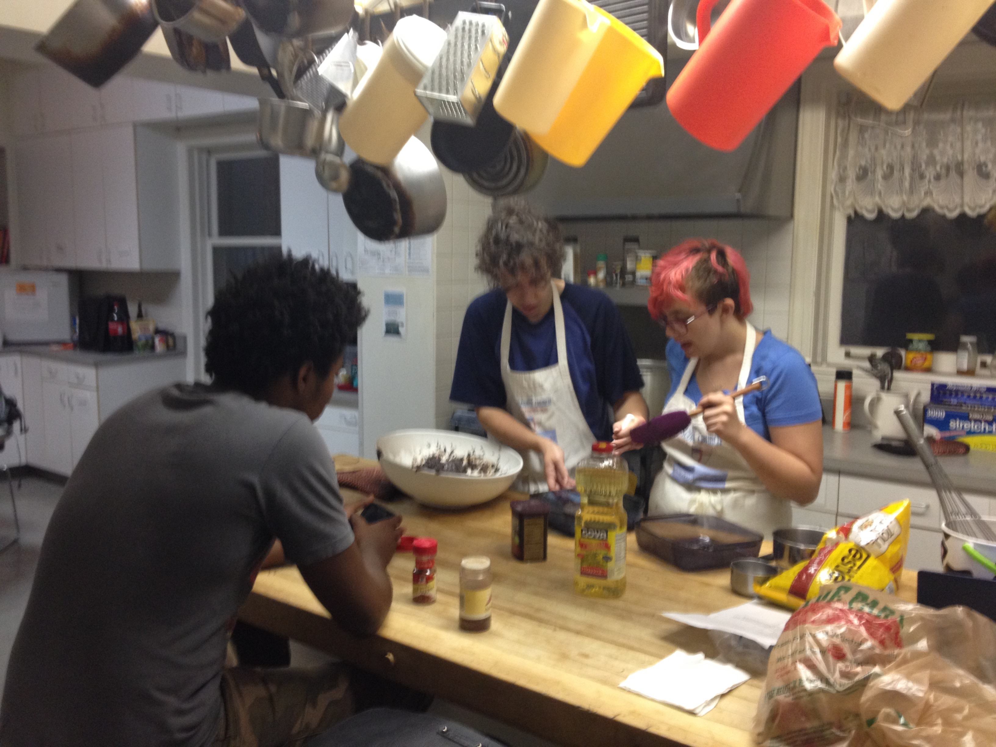 The students cooking together, gathered around the island in Brent House's kitchen.